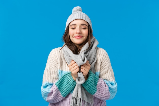 幸福、夢、クリスマス気分コンセプト。冬の帽子、セーター、首の周りのスカーフに触れる陽気な魅力的な官能的な若い女性、目を閉じて新鮮な空気を吸い込む、雪の天気をお楽しみください
