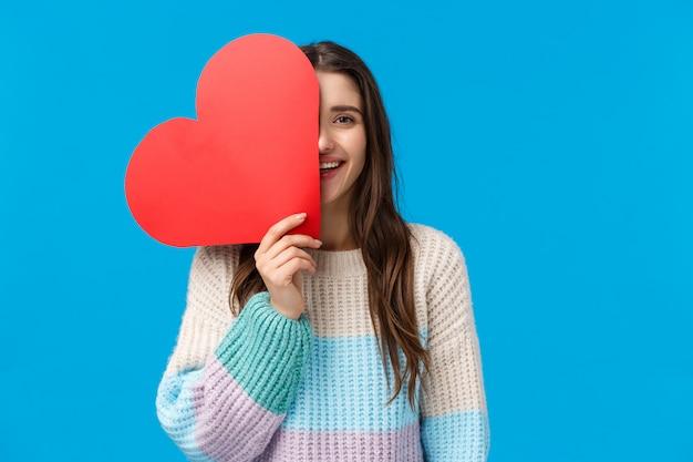 Время сказать я люблю тебя. веселая мечтательная и милая кавказская брюнетка покрывает половину лица с большим красным сердечным знаком, улыбается, выражает привязанность и вычурность в день святого валентина, получает милый подарок