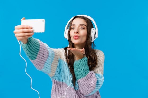 ロマンス、冬休み、女性のコンセプト。冬のセーターの魅力的で官能的で軽薄な若いブルネットの女性、大きなヘッドフォンを着て、スマートフォンを保持し、電話でキスを吹く