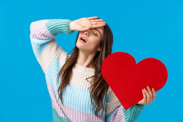 愛情、情熱、関係の概念。冬のセーターで魅力的なロマンチックな女性、額に手をため息をついて、目を閉じて、大きな赤いハートを押し、愛から彼女の心を失う、青