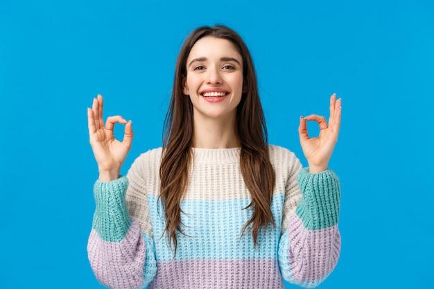 冬のセーターで幸せなカリスマ的なゴージャスな女性、はい、申し分なく、いいジェスチャーを見せ、優れた映画を評価し、完璧な贈り物、冬のスキーリゾートで素晴らしい休日を過ごす、ブルー