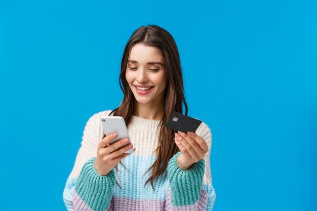 リラックスした上半身の肖像画、冬のセーターでゴージャスな女性の笑顔、購入の支払い、アプリで友人にお金を送る、請求情報、アプリケーションでのクレジットカード番号の挿入、スマートフォンの保持