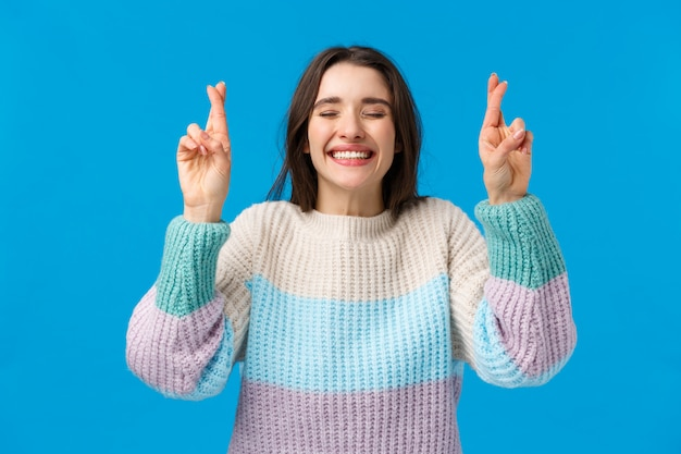 冬のセーターの楽観的なかわいい女性の少女、信仰の夢が叶う、広く笑顔、幸運のために指を組んで願いを作る目を閉じて、祈り、青