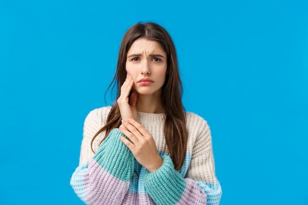 上半身撮り悲しい愚かな少女、歯のトラブル、痛みから目をそらす顔をしかめる、歯痛を感じるように頬に触れる、予約歯科医、青に立っている