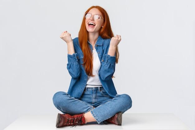 スタジオポートレート満足、幸せと安心の赤毛の女性、十代の少女が受賞を祝って、足を組んで床に座って勝利、拳ポンプはい、笑顔、白