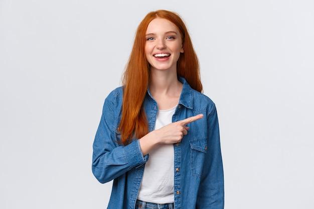 Беззаботная, дружелюбная и счастливая общительная рыжеволосая женщина в джинсовой рубашке, указывая пальцем вправо и смеясь над камерой с сияющей улыбкой, стоя белая, обсуждая, общается с командой