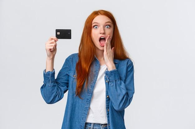 Удивительные скидки, концепция банковского обслуживания. удивленный портрет удивленной и удивленной симпатичной рыжеволосой женщины, держащей кредитную карточку, реагирует удивленно на прекрасную возможность, дешевая распродажа