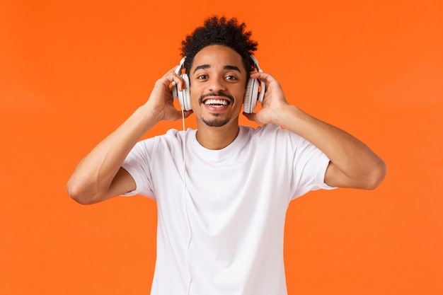 Концепция счастья, технологии и гаджеты. привлекательный счастливый харизматичный афроамериканец в белой футболке, слушающий музыку в наушниках, радостный улыбающийся фотоаппарат, как подарок, оранжевый