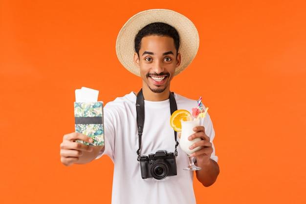 帽子で笑顔のアフリカ系アメリカ人の男、一緒に旅行、パスポートと航空券を与え、カクテルを飲み、休暇を楽しんで、高級リゾート、オレンジの完璧な休日に満足