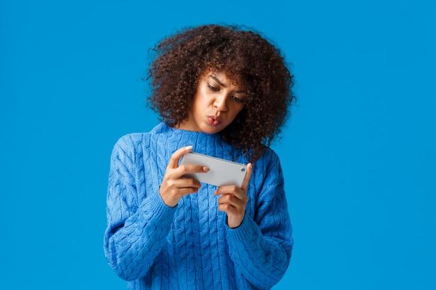 深刻な焦点を当てたかわいいアフリカ系アメリカ人の女の子がスマートフォンで面白いゲームをプレイし、携帯電話を回し、電話を水平に保持し、困惑し、困惑し、青く立っている