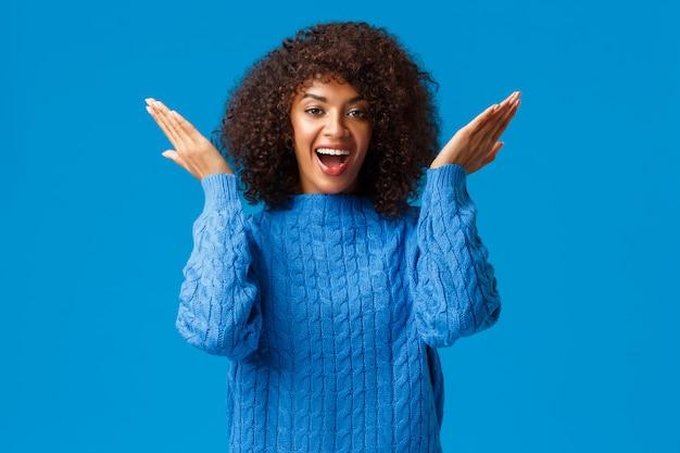 Милая и игривая, забавная счастливая афроамериканская женщина с афро-стрижкой в зимнем свитере, открытыми глазами, чтобы увидеть сюрприз к празднику, секретный подарок дня святого валентина, глядя удивленно и восхищенно, синий