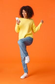 フルレングスの垂直ショット陽気なかわいい技術は、アフリカ系アメリカ人の現代の少女をアフロのヘアカットで中毒にし、ジャンプして勝利し、スマートフォンから素晴らしいニュースを読んでいる、オレンジ