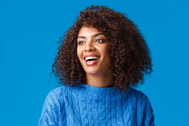 Портрет крупным планом беззаботной счастливой и восхищенной, красивой афроамериканской женщины, наслаждающейся прекрасными праздниками, посещением горнолыжного курорта, созерцанием снежной погоды, взглядом влево и улыбкой довольной