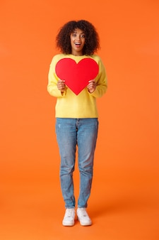 Полнометражный вертикальный снимок прекрасной харизматичной и мечтательной афроамериканки в свитере, джинсах, с большим красным сердцем в поисках родственной души, даты на день святого валентина, оранжевого цвета