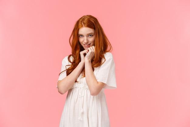 Милая рыжая женщина в белом платье, действующая глупо и мило