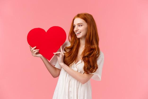 大きな赤いハートのカードを見て、柔らかい白いドレスで赤毛の女の子