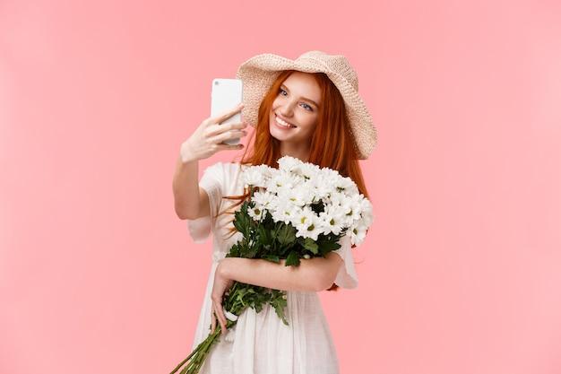 Рыжая девушка с красивым цветочным букетом в белом платье, принимая селфи