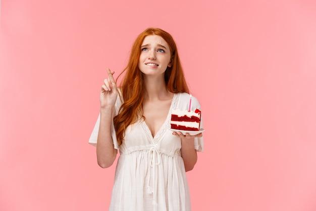 赤いベルベットのケーキと交差させた指で赤毛の女の子