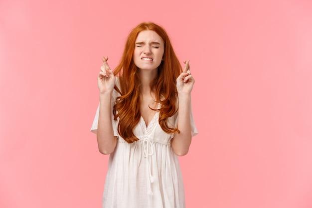交差させた指で若い赤毛の女の子