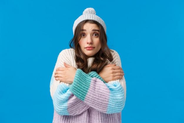 Брюнетка в зимней шапке и свитере чувствует себя холодно