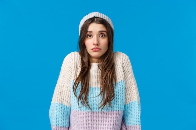 冬の帽子とセーターの寒さを感じてブルネットの女性