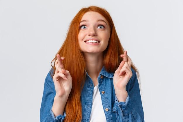 空を見上げて、指で願いを作る楽観的な赤毛の女の子を渡った