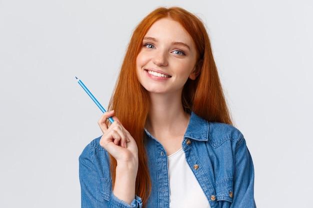 Рыжая девушка держит цветной карандаш