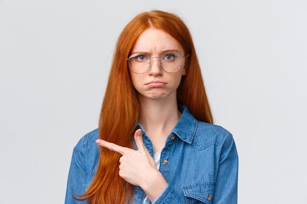 怒りの表現で左を指している赤毛の女の子