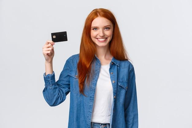 Веселая рыжая девушка держит кредитную карту и улыбается