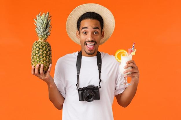 Молодой человек, держащий ананас и коктейль