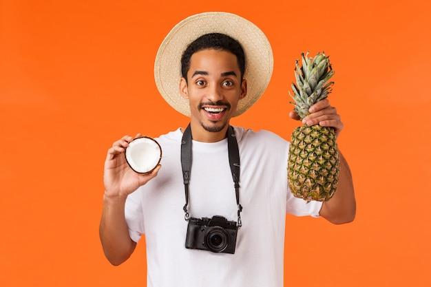 トロピカルフルーツを保持しているアフリカ系アメリカ人の観光客