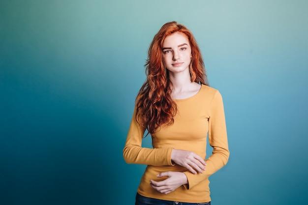 ファッションコンセプト - ヘッドショットカメラを見て自信を持って顔と黄色のセーターと幸せなジンジャー赤毛の女の子の肖像画。パステルフィルムの青い背景。スペースをコピーします。