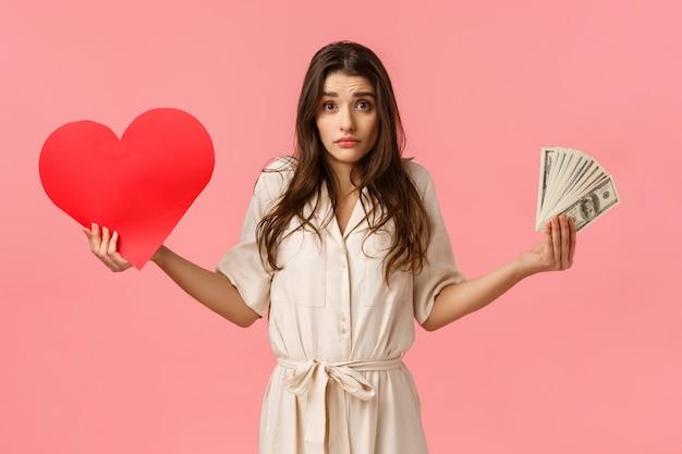 Нерешительная и неуверенная, милая прекрасная современная женщина не может решить, что важно, пожимает плечами, смотрит в замешательстве, держит сердечную карточку и деньги, не знаю, что правильно, под вопросом на розовом фоне