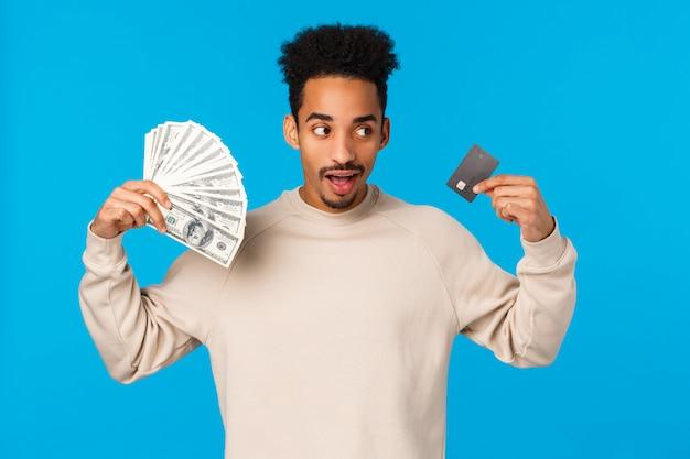 Удачливый и удивленный афроамериканский стильный хипстерский парень, чувствующий себя богатым, получил деньги, открыл счет в банке с депозитом, играл с наличными деньгами, держал деньги и кредитную карту, стоял синий фон