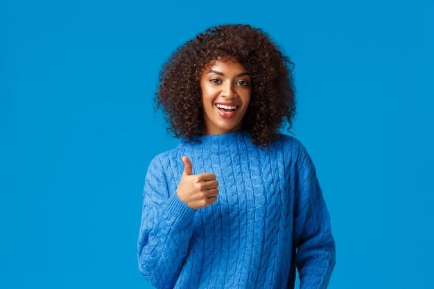 Хороший выбор, одобряю. симпатичная симпатичная афроамериканская женщина с афро-стрижкой в зимнем свитере, показывающая поддержку большого пальца, поощряет друга, хорошо поработала, довольна стоящим синим фоном