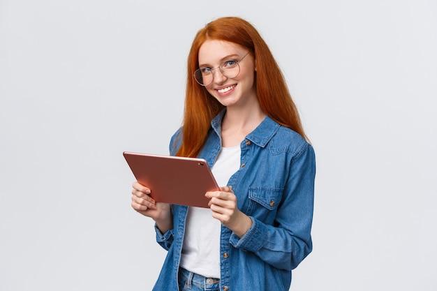 プロ意識、仕事、そして人々のコンセプト。メガネの若い陽気な魅力的な女性赤毛、デジタルタブレットを押しながらカメラに笑顔で幸せな自信を持って
