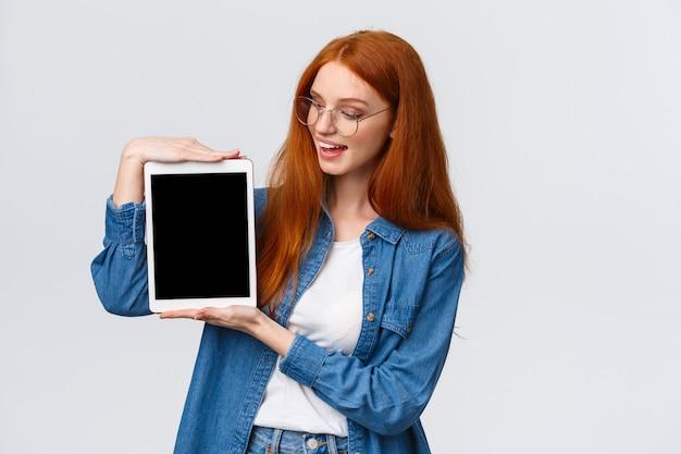 技術と人のコンセプトです。魅力的な創造的な若い赤毛の女の子が大学のデザインプロジェクトを作成し、デジタルタブレットを保持し、デバイスの画面に何かを紹介します。
