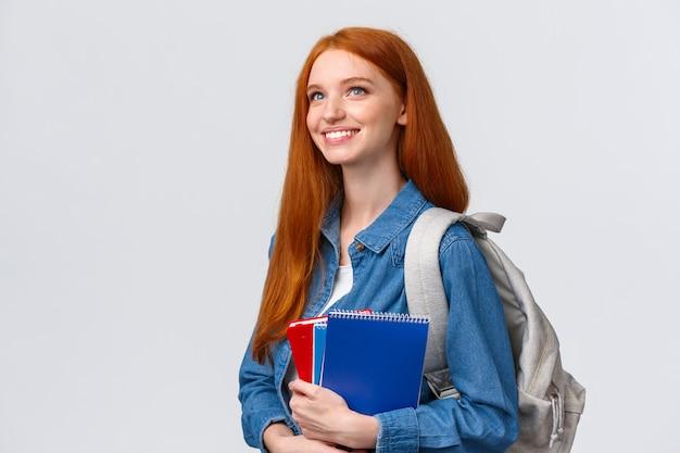 Молодежь, подростки и концепция образования. решительная симпатичная мечтательная и жизнерадостная улыбающаяся рыжая студентка с тетрадями и рюкзаком с нетерпением ждет новой темы в классе