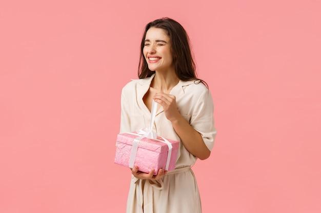 Концепция счастья, торжества и вселенной. счастливая и беззаботная жизнерадостная девушка-распутница разворачивает милый подарок, улыбается и смеется с закрытыми глазами, чувствуя радость, открытый подарок на день рождения