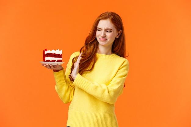 Нет, спасибо, не хочу. милая рыжая девушка пытается устоять перед искушением откусить вкусные сладости, держа вкусный торт и показывая стоп, отказ или отказ с морщась лицом, выражать отвращение, неприязнь