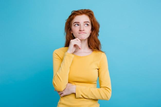 Портрет счастливый рыжий рыжий волосы девушка с веснушками, улыбаясь, глядя на камеру. пастель синий фон. копирование пространства.