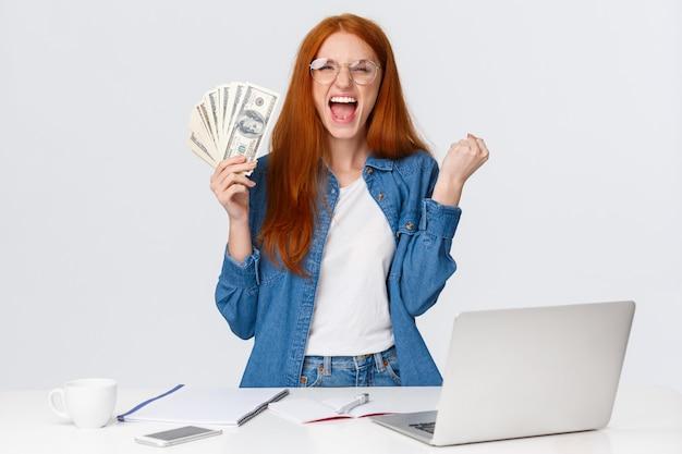 Торжествующая и веселая, привлекательная счастливая рыжая женщина кричит да, ура, держащая большие деньги