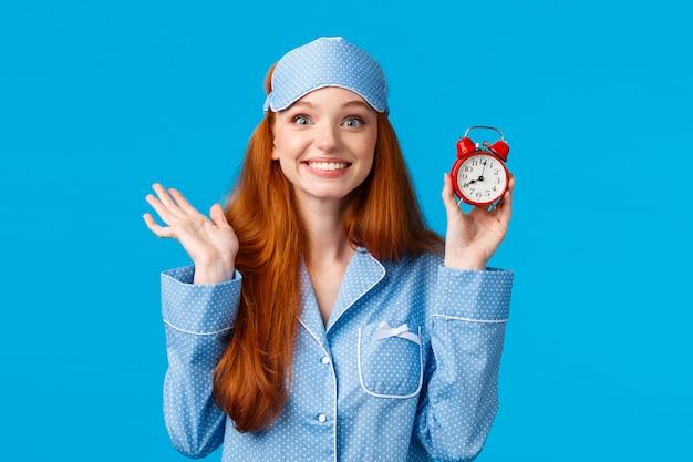 Веселая и восторженная рыжеволосая девушка не хочет спать, ставит будильник, держит красные часы
