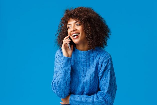 カリスマ的な魅力的な幸せなアフリカ系アメリカ人女性が電話に出て、楽しく笑って