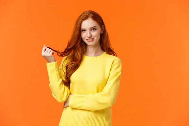 ゴージャスな軽薄でかわいい若いモダンな赤毛の生意気な女の子、髪にカールをローリング