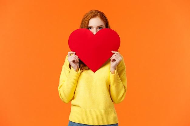 バレンタインの日にかわいいロマンチックで赤面する女の子が感情を表現し、大きな心の後ろに恥ずかしがり屋の顔を隠します