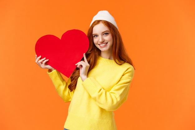 Веселая милая рыжая девушка держит большое красное сердце