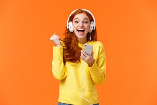 Ура да новая песня. привлекательный веселый и возбужденный рыжий женщина кулак насос в радости