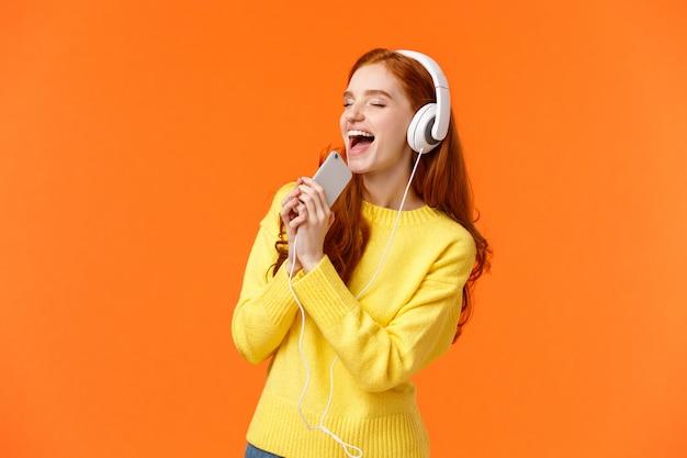 好きな曲を聴きながら女性が流された。かなり赤毛の女性が新しいヘッドフォンで音楽を楽しむ