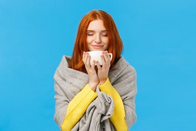目を閉じて喜んで香りのコーヒーの素敵なホットカップを楽しむ女性